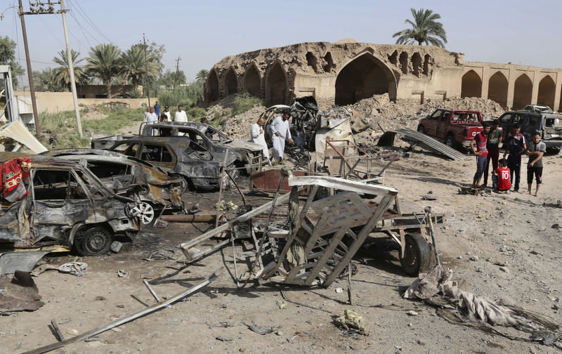 Civilians inspect the scene of a deadly Friday night suicide car bombing at a busy market in Khan Beni Saad, Iraq.