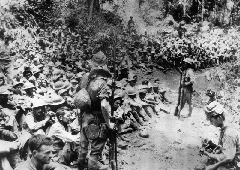 In this 1942 file photo provided by U.S. Marine Corps, Japanese soldiers stand guard over American war prisoners just before the start of the Bataan Death March following the Japanese occupation of the Philippines (U.S. Marine Corps via AP, File)