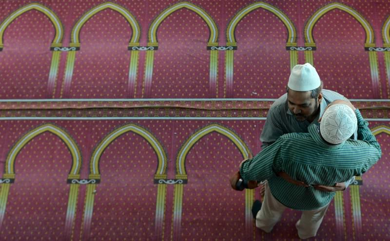 Nepalese Muslim devotees hug after offering early morning Eid al-Fitr prayers at Kashmiri Mosque in Kathmandu.