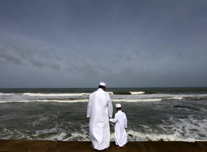 A Sri Lankan Muslim father and son stand in front of the sea during morning prayers of Eid al-Fitr celebrations marking the end of Ramadan.