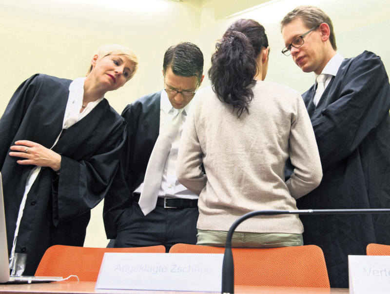 Anja Sturm (L), Wolfgang Stahl (C) and Wolfgang Heer (R) with Beate Zschaepe who is seen with her back turned in 2013 at a Munich courtroom.