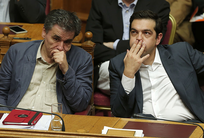 Greek Prime Minister Alexis Tsipras (Right) sits next to Finance Minister Euclid Tsakalotos (L) as he attends a parliamentary session in Athens, Greece July 16, 2015.