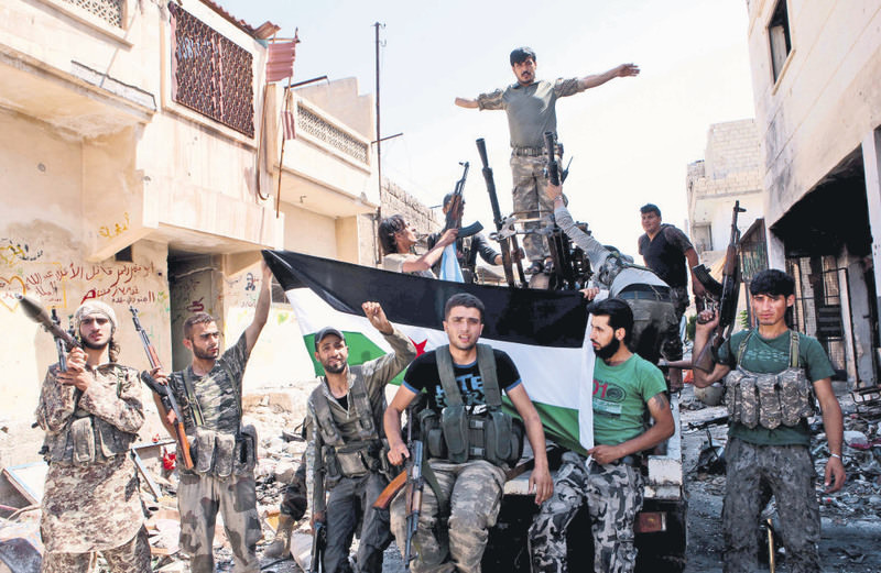 Members of the Free Syrian Army fighting against the Assad regime under harsh conditions show their strength in captured areas.