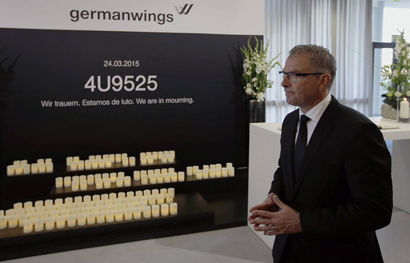 Lufthansa CEO Carsten Spohr walks by a memorial place after he signed a condolence book for the victims of the Germanwings plane crash in FrancE (AP Photo)