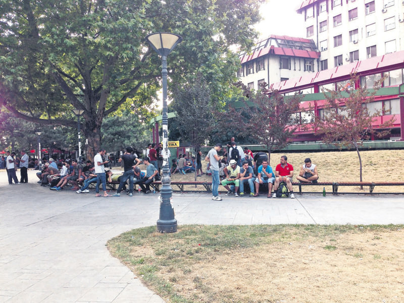 Migrants from several nations sit in parks.