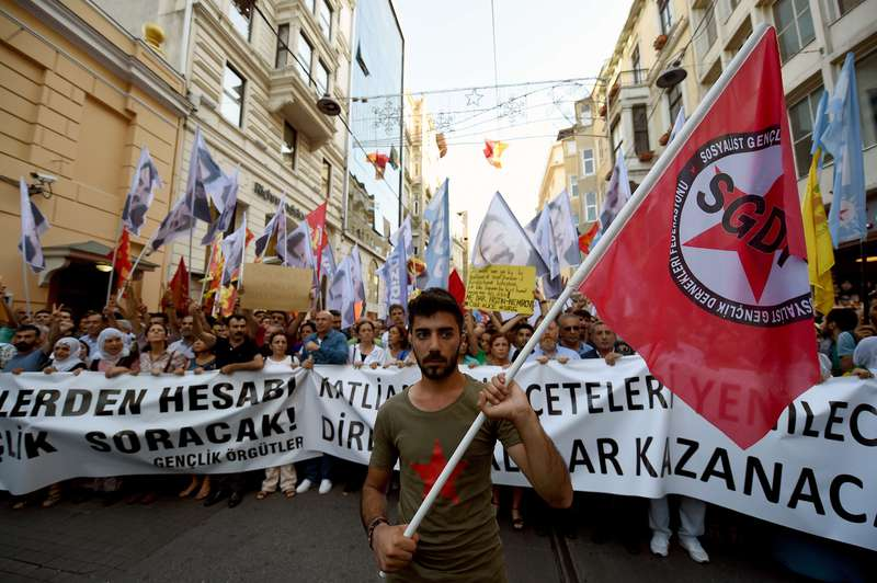 A protester holds a flag of attacked left-wing group SGDF (AFP Photo)