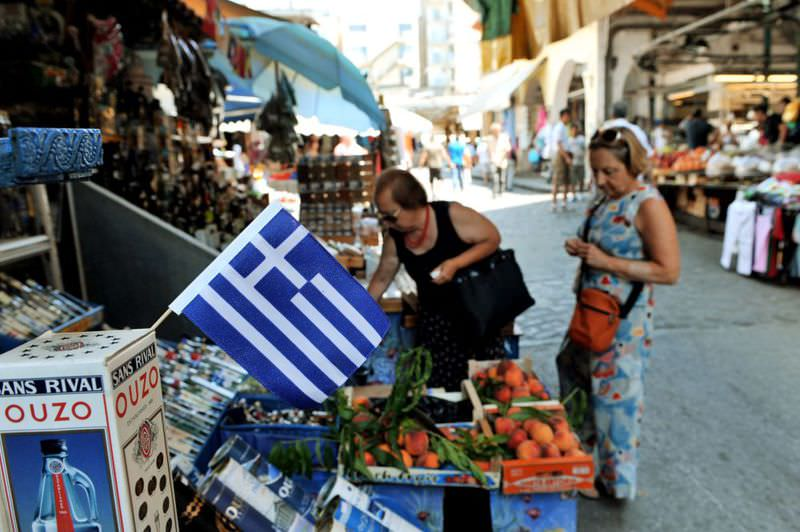 Customers stand at a shop on the streets of Thessaloniki province in Greece.