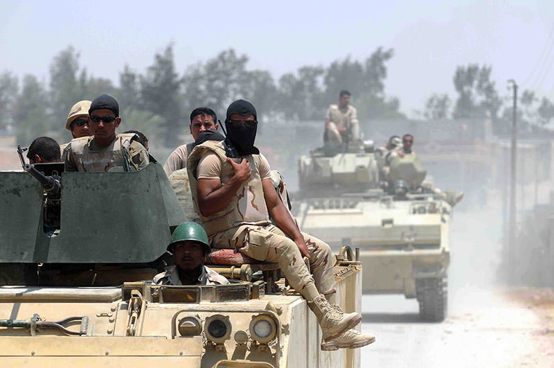 A picture made available 23 July 2015 shows members of the Egyptian armed forces in armored vehicles patrolling a street near the town of Sheikh Zuweid, in the north of Sinai, Egypt, 13 July 2015 (EPA photo)