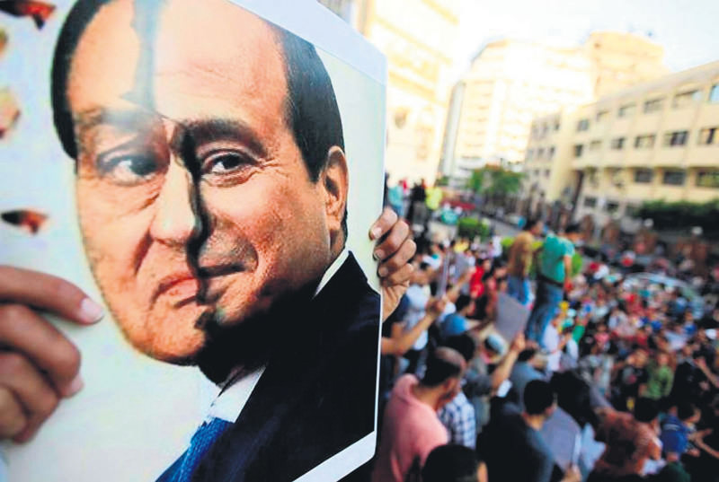 One of the thousands of Egyptians who protest el-Sissi and the coup almost every Friday across the country holds a sign.