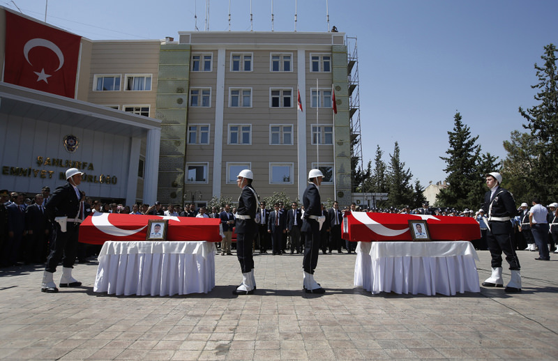 Turkish police officers stand in attention in front of the coffins of police officers Feyyaz Yumuu015fak and Okan Acar, who were found shot dead in their home, during a funeral procession in u015eanlu0131urfa province, Turkey.