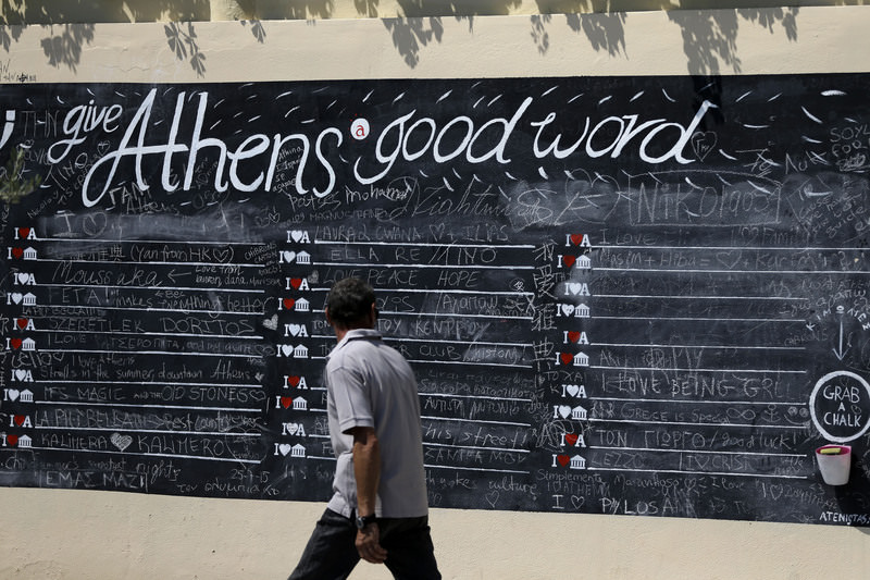 A pedestrian looks at a board where people can write their comments about the Greek capital, displayed on a wall in Athens, on July 27. The government has already begun imposing new austerity measures demanded in return for the new bailout