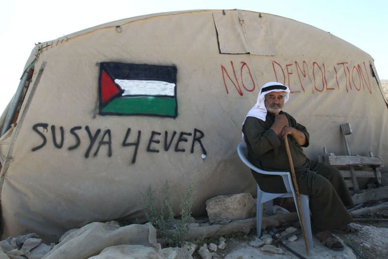 A villager sitting outside his tent in Susya during a protest earlier this month against the village's demolition. The village is largely tents and huts.