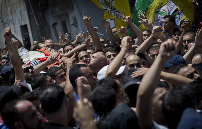 Mourners chant slogans while carrying the body of Palestinian Mohammed Lafi Abu Latifeh, 20, who was killed during an Israeli arrest raid, during his funeral procession.