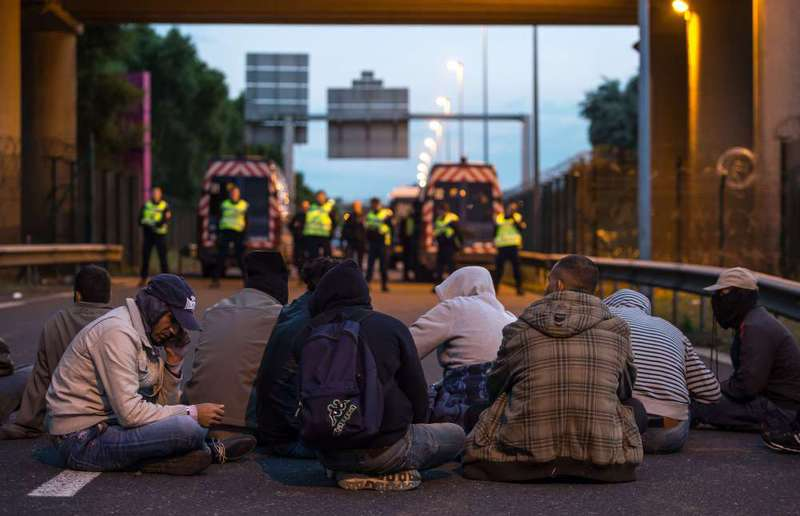 French gendarmes stand facing a group of seated migrants as they block their way to the Eurotunnel site in Coquelles near Calais, northern France.