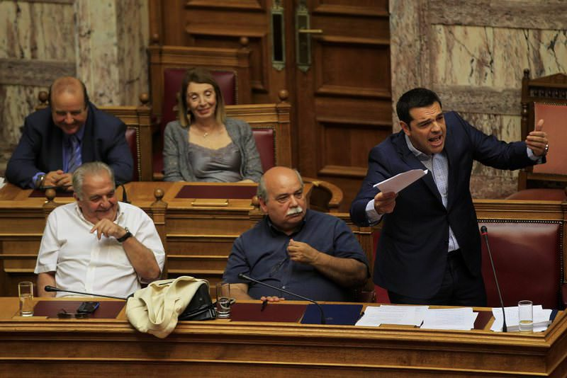 Greek Prime Minister Tsipras (R) speaks next to other ministers in Parliament during Prime Minister's Question Time in Athens on Friday.