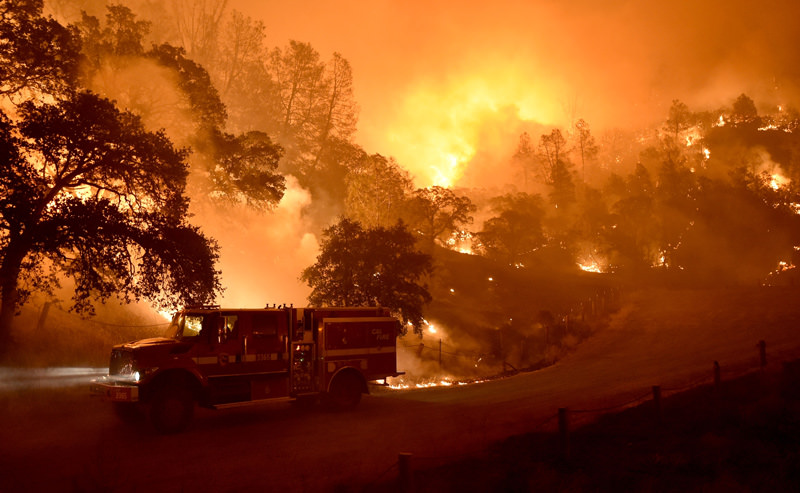 A Cal Fire truck is driven away from flames as the Rocky fire burns near Clear Lake, California on August 2, 2015. The fire has charred more than 54,000 acres. AFP PHOTO
