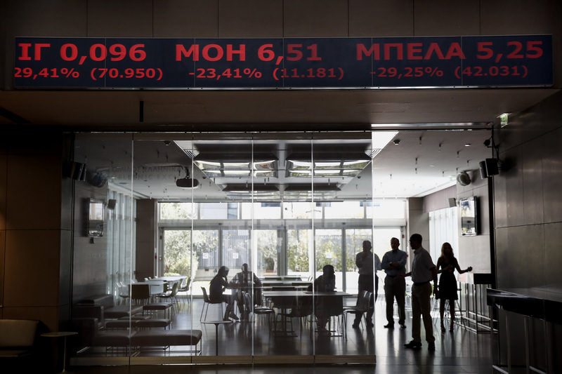 Employees of the Athens Stock Exchange talk as they stand behind a ticker screen where stock prices are on display in Athens on Monday.
