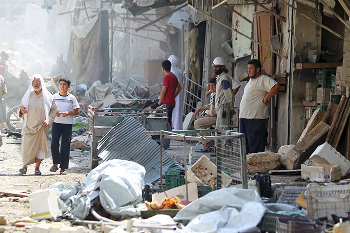 People inspect the damage after a Syrian army fighter jet crashed into a busy marketplace in the rebel-held northwestern town of Ariha August 3, 2015(Reuters Photo)