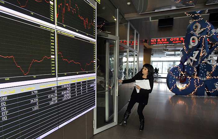 Woman opening a door next to screens displaying Greek stock indicies in Athens, Greece (EPA Photo)