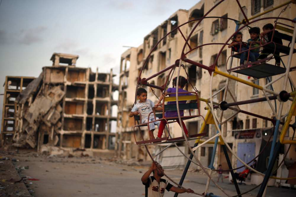 Palestinian children enjoy a ride on a ferris wheel near residential buildings destroyed by Israeli bombs in Gaza.