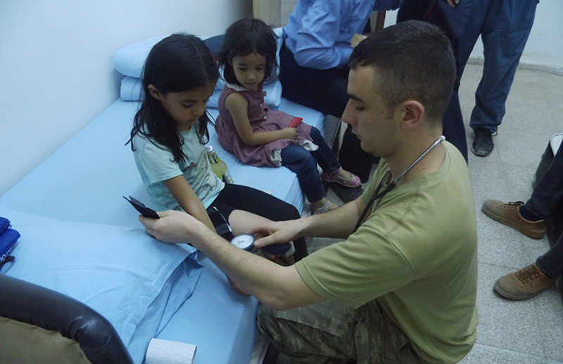 Six-year-old Nuru015fin Buldan receiving medical treatment from a Turkish soldier Turkey's southeastern Hakkari province on August 4, 2015 (DHA Photo)