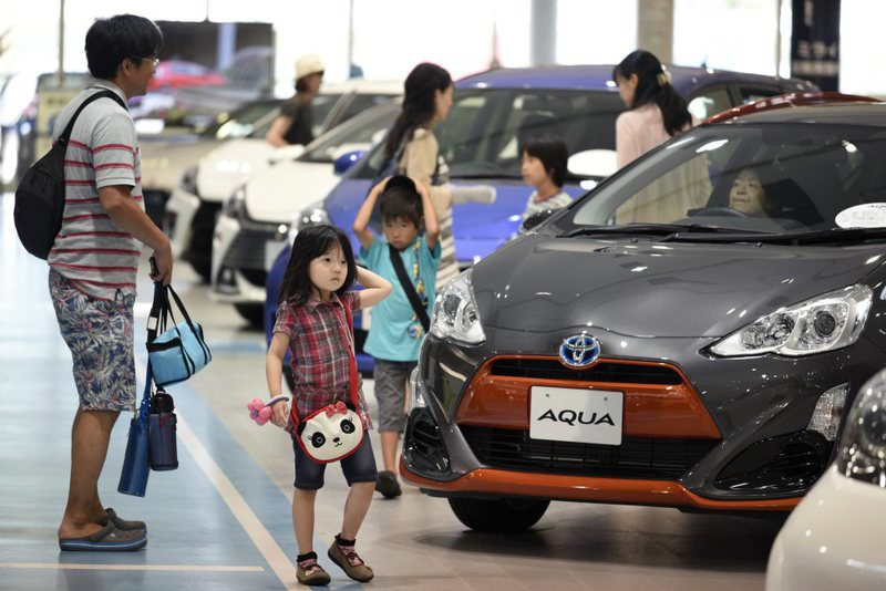 Visitors look at Toyotas displayed at the company's showroom in Tokyo, Japan.