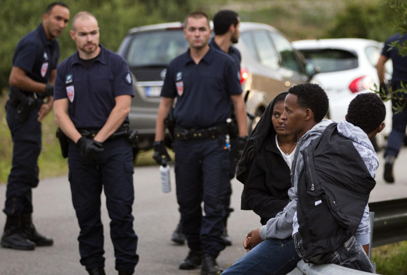 Police officers blocking the road stand next to migrants as they try to access train tracks that lead to the Channel Tunnel in Calais.
