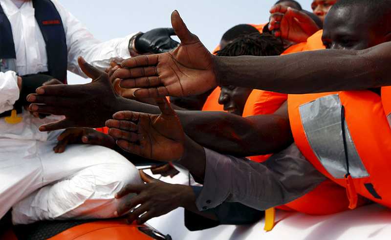 Some 118 migrants were rescued from a rubber dinghy off Libya on Monday morning. Migrants reach out to grab hold of rescuers on the boat off the coast of Libya, August 3 (Reuters photo)