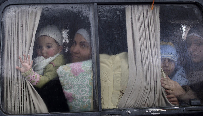 Syrian refugees, who fled their home in Idlib due to a government airstrike, look out of a vehicle's window just after crossing the border from Syria to Turkey.