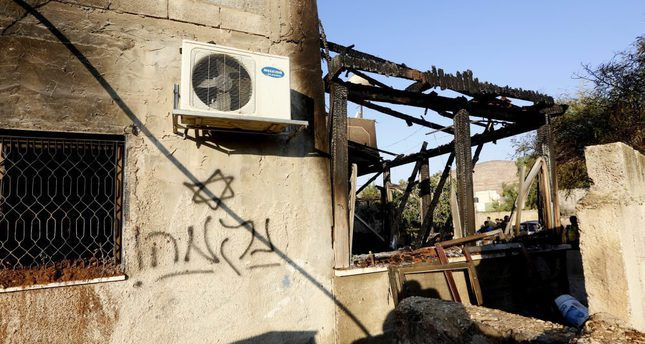 Graffiti reading in Hebrew revenge seen on the wall of the fire damaged house in the West Bank village of Duma near Nablus City