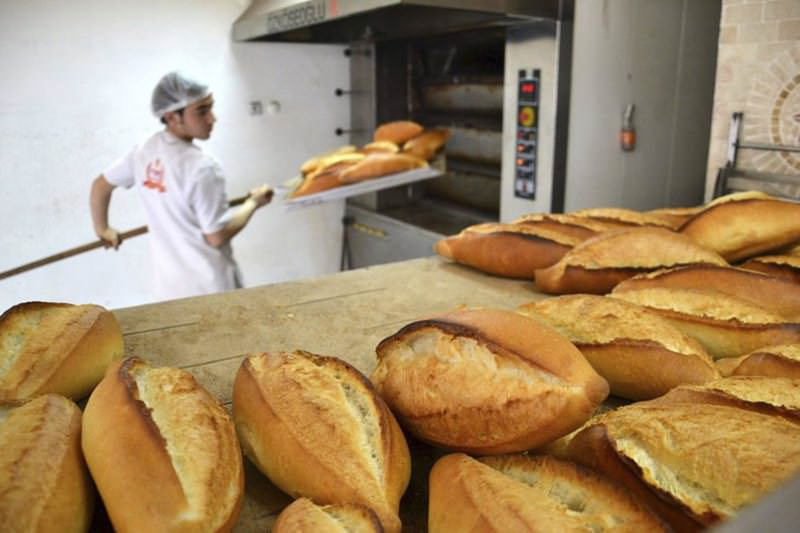 A baker removing loaves of bread from the oven. Over-production of bread by bakeries is among the leading causes of bread waste.