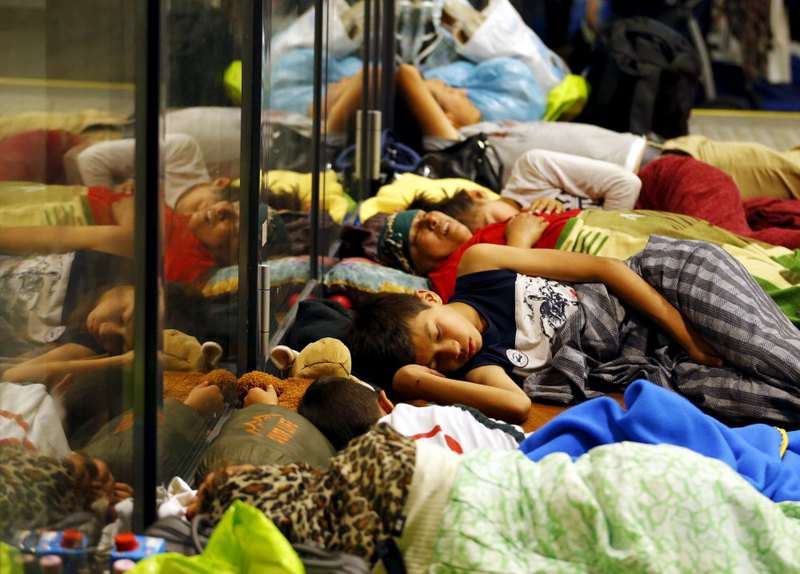 Migrants sleep outside a train station in Budapest, Hungary, Aug. 3.