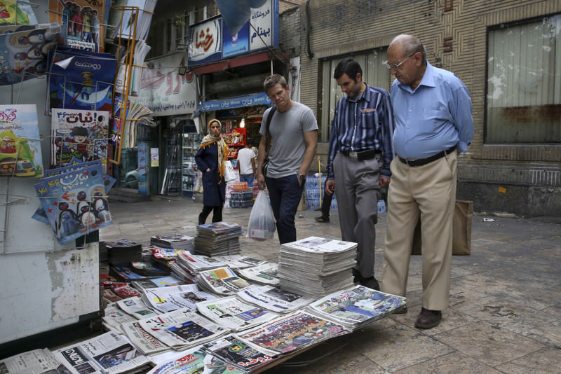 People read front pages of Iranian newspapers at a news stand in the Tajrish Sq. northern Tehran, Iran.