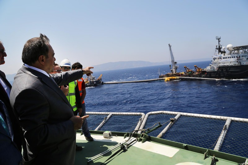 Forestry and Water Affairs Minister Veysel Erou011flu points on the vessel where the last parts of the pipeline were joined together and submerged off the coast of Kyrenia.