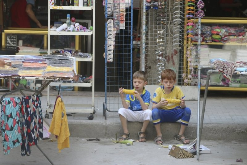 Two boys sit on a pavement as they eat corn in Aleppo's eastern district of Tariq al-Bab, Syria .