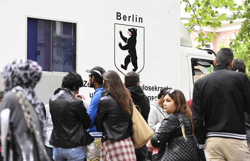 Refugees queue up in front of a medical truck in the yard of the ,State Office of Health and Social Affairs, in Berlin's Moabit district (AFP Photo)