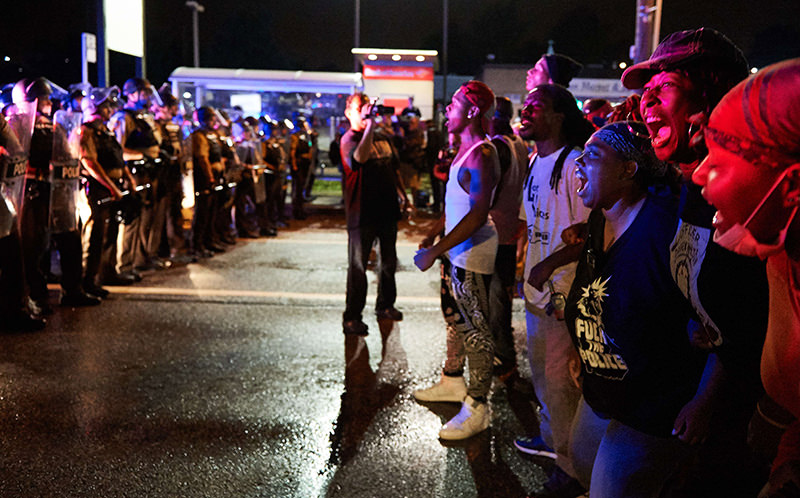 A group of demonstrators (R) yells in front of police officers during a protest march in Ferguson, Missouri. (AFP Photo)