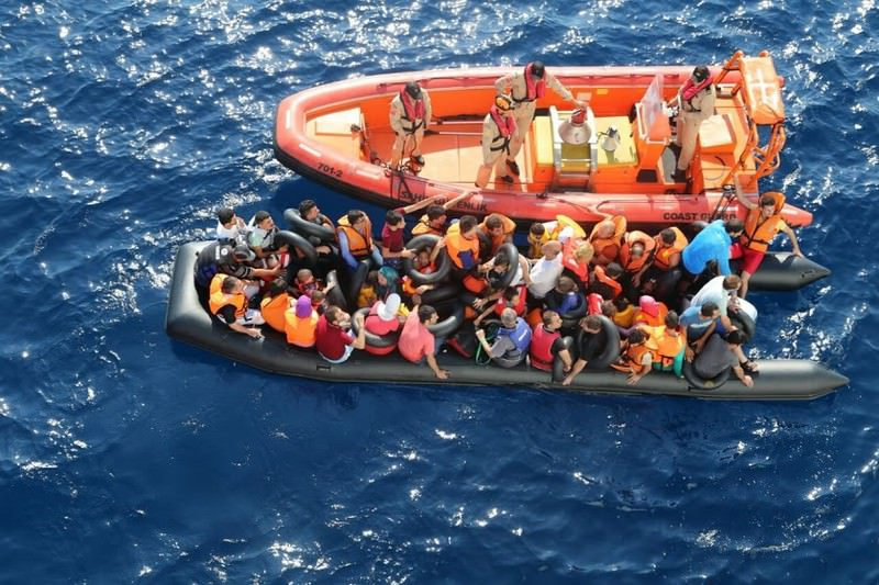Illegal immigrants huddled in a boat next to a Coast Guard boat. Every year, thousands try to cross to Greek islands from Turkey.