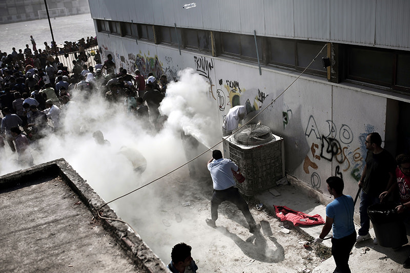 Policemen (foreground, R) try to disperse hundreds of migrants by spraying them with fire extinguishers during a gathering for a registration procedure at the stadium on the Greek island of Kos, on August 11, 2015 (AFP photo)