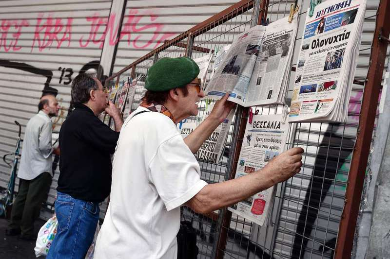 People read at newspapers in Athens. Greece's third bailout, whose details were agreed to with international creditors, will total around 85 billion euros over three years.