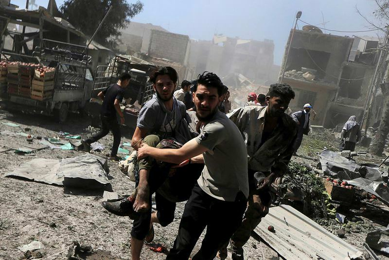 Men transport a casualty after Syrian warplanes pounded a busy market place in Douma, rebel-held Damascus suburb.