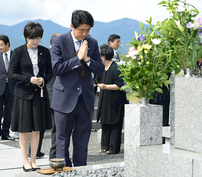 Japanese Prime Minister Shinzo Abe, accompanied by his wife Akie, left, prays at his ancestors' grave in Nagato, western Japan, Friday, Aug. 14, 2015 (Yuta Omori/Kyodo News via AP)