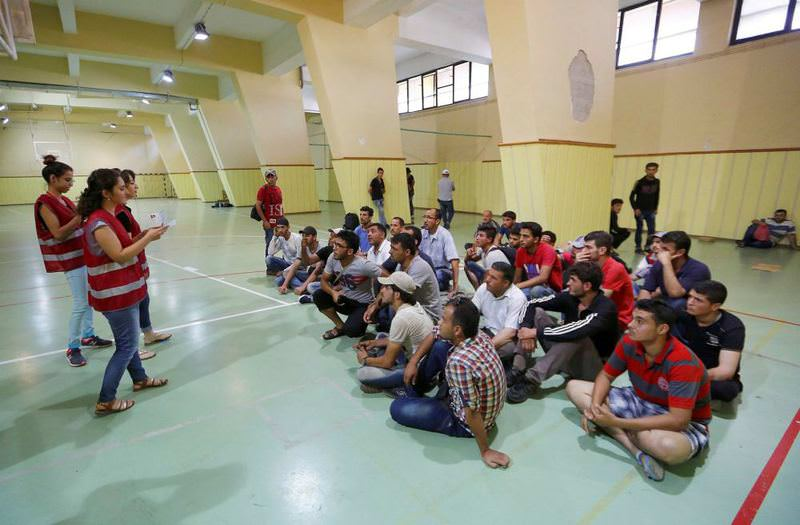 Officials from Interior Ministry's Migration Management Directorate informing undocumented Syrians gathered in a sports hall in u0130zmir on registering for their transfer to refugee camps.
