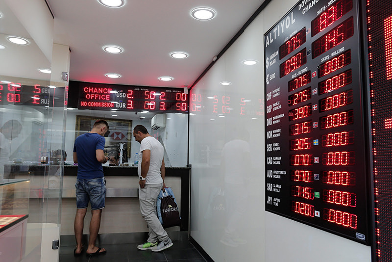 People exchange their money at a currency exchange booth in Istanbul, Turkey, 13 August 2015 (EPA photo)