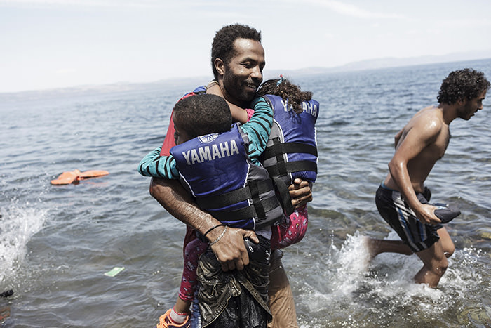 A migrant carries his two children as he gets off of an inflatable boat after arriving on the Greek island of Lesbos after crossing the Aegean sea from Turkey to Greece on August 14, 2015 (AFP Photo)