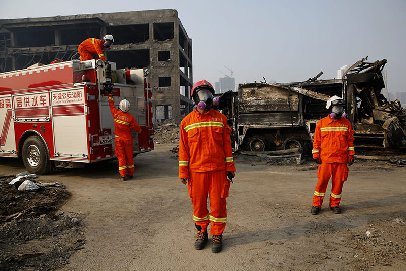 Firemen wearing gas masks search the area of a huge explosion that rocked the port city of Tianjin, China, 15 August 2015 (EPA photo)