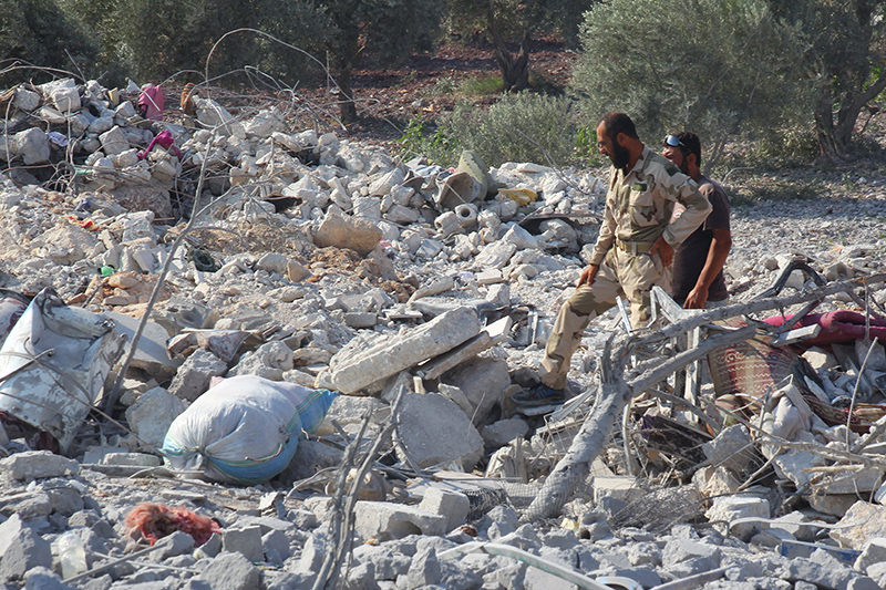 Rebel fighters from ,Jaysh al-Sunna, inspect the damage at a weapons factory operated by them that was targeted in what activists say were U.S.-led air strikes on Atmeh village in Idlib countryside August 12, 2015 (Reuters Photo)