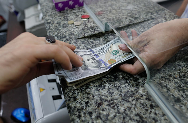 A man exchanges money at a currency exchange booth in Istanbul, Turkey, 13 August 2015 (EPA photo).