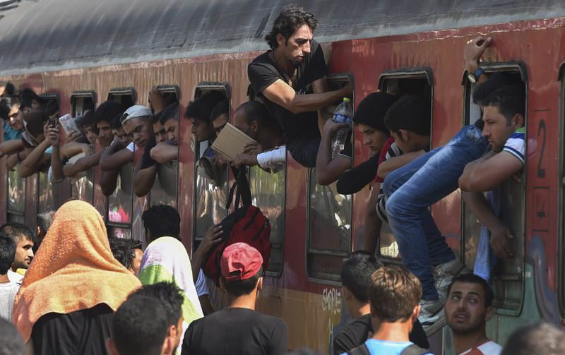 A migrant gets out of a full train heading to the Serbian border at the train station in Gevgelija, Macedonia on Aug. 16