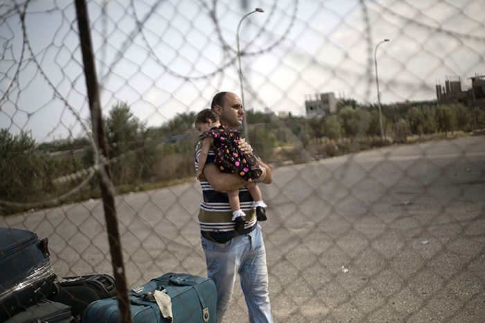 A Palestinian man carries a baby as he waits at the Rafah border crossing in the southern Gaza Strip for permission to enter Egypt on August 17, 2015 (AFP Photo)